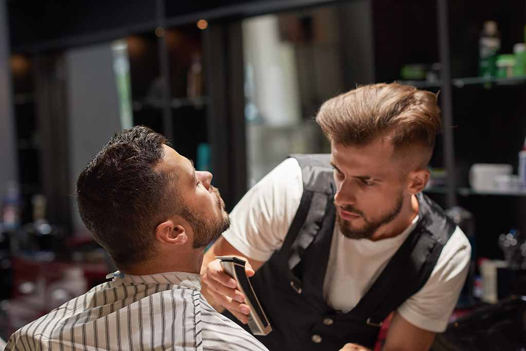 Concentrated male hairdresser holding trimmer in hands.
